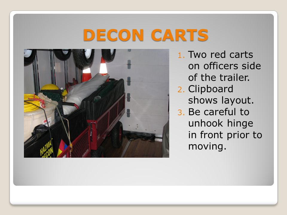 DECON CARTS 1. Two red carts on officers side of the trailer.