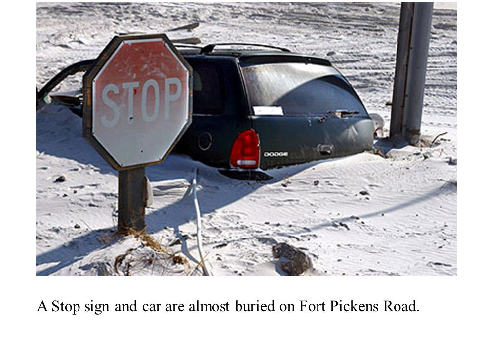 A Stop sign and car are almost buried on Fort Pickens Road.