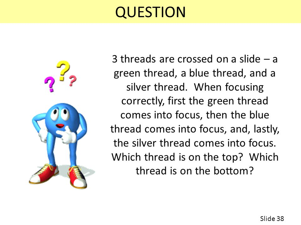 3 threads are crossed on a slide – a green thread, a blue thread, and a silver thread.