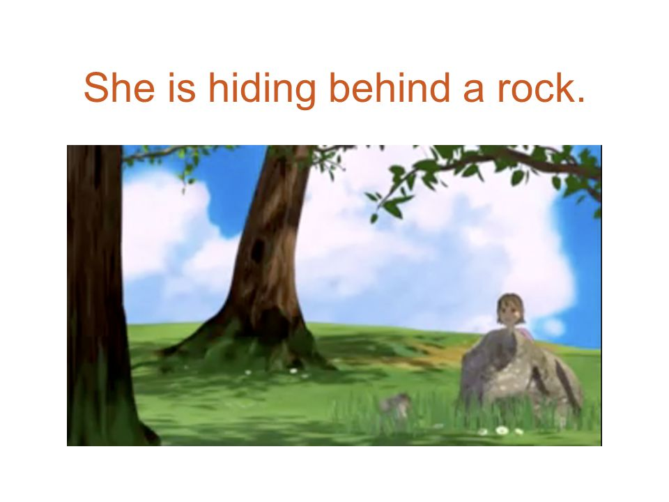 She is hiding behind a rock.