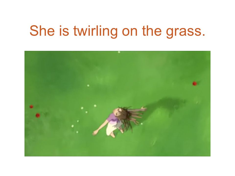 She is twirling on the grass.