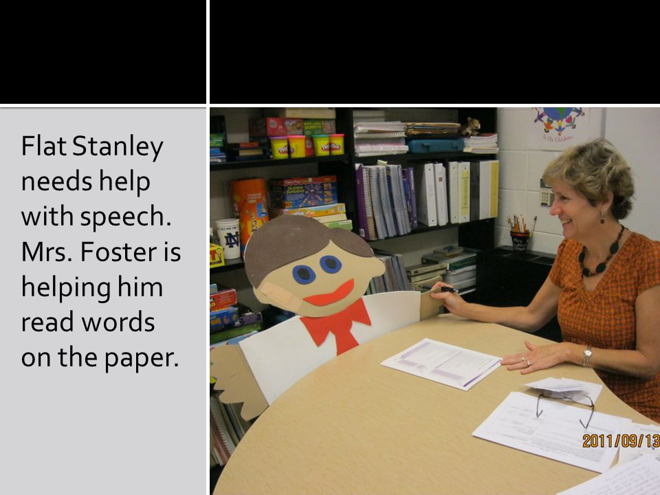 Flat Stanley needs help with speech. Mrs. Foster is helping him read words on the paper.