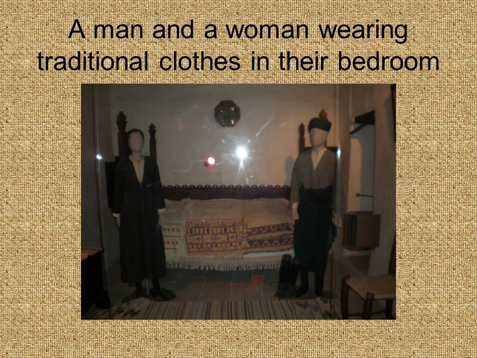 A man and a woman wearing traditional clothes in their bedroom