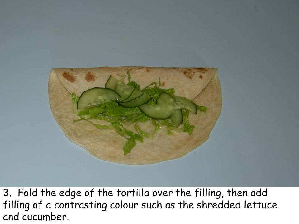 3. Fold the edge of the tortilla over the filling, then add filling of a contrasting colour such as the shredded lettuce and cucumber.