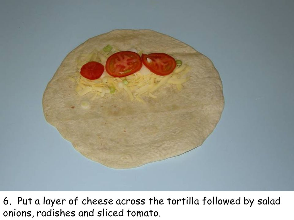 6. Put a layer of cheese across the tortilla followed by salad onions, radishes and sliced tomato.