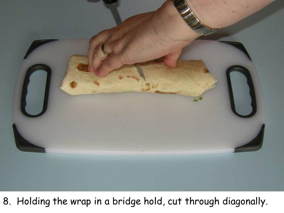 8. Holding the wrap in a bridge hold, cut through diagonally.