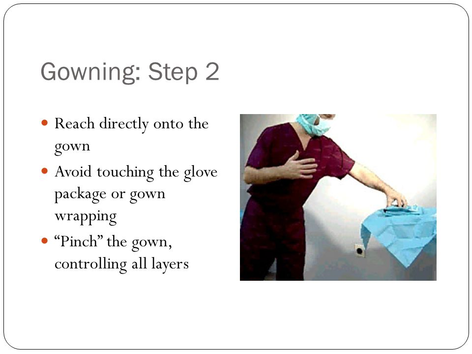"""Gowning: Step 2 Reach directly onto the gown Avoid touching the glove package or gown wrapping """"Pinch"""" the gown, controlling all layers"""