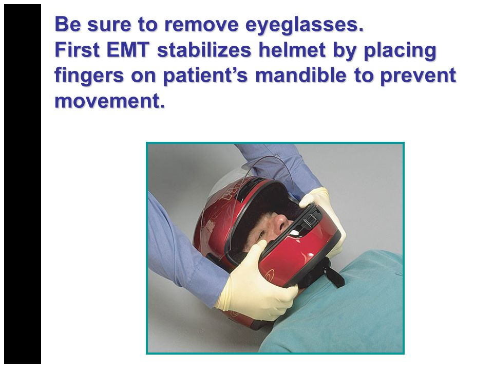 Be sure to remove eyeglasses. First EMT stabilizes helmet by placing fingers on patient's mandible to prevent movement.