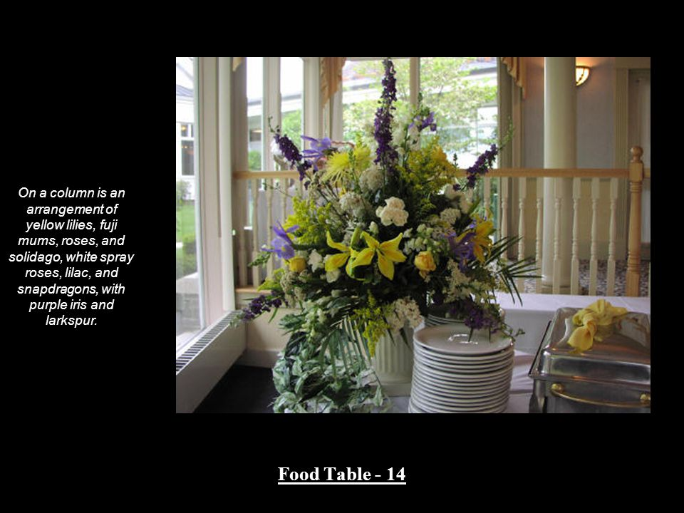 Food Table - 14 On a column is an arrangement of yellow lilies, fuji mums, roses, and solidago, white spray roses, lilac, and snapdragons, with purple iris and larkspur.