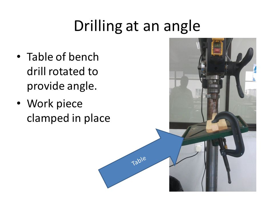 Drilling at an angle Table of bench drill rotated to provide angle.