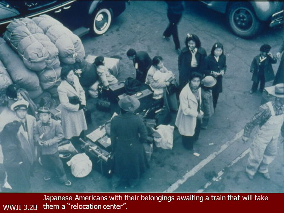 WWII 3.2B Japanese-Americans with their belongings awaiting a train that will take them a relocation center .