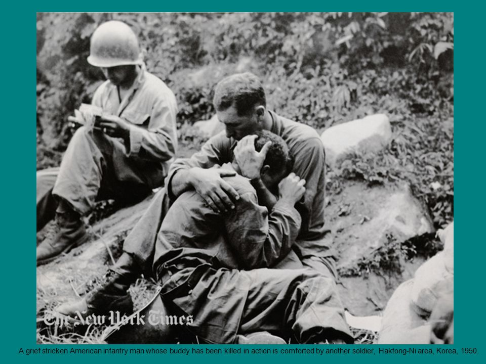A grief stricken American infantry man whose buddy has been killed in action is comforted by another soldier, Haktong-Ni area, Korea, 1950.