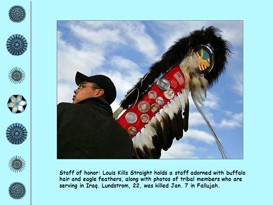 Staff of honor: Louis Kills Straight holds a staff adorned with buffalo hair and eagle feathers, along with photos of tribal members who are serving in Iraq.