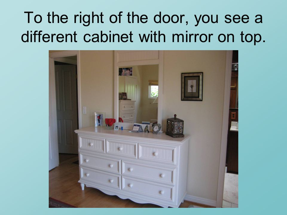 To the right of the door, you see a different cabinet with mirror on top.