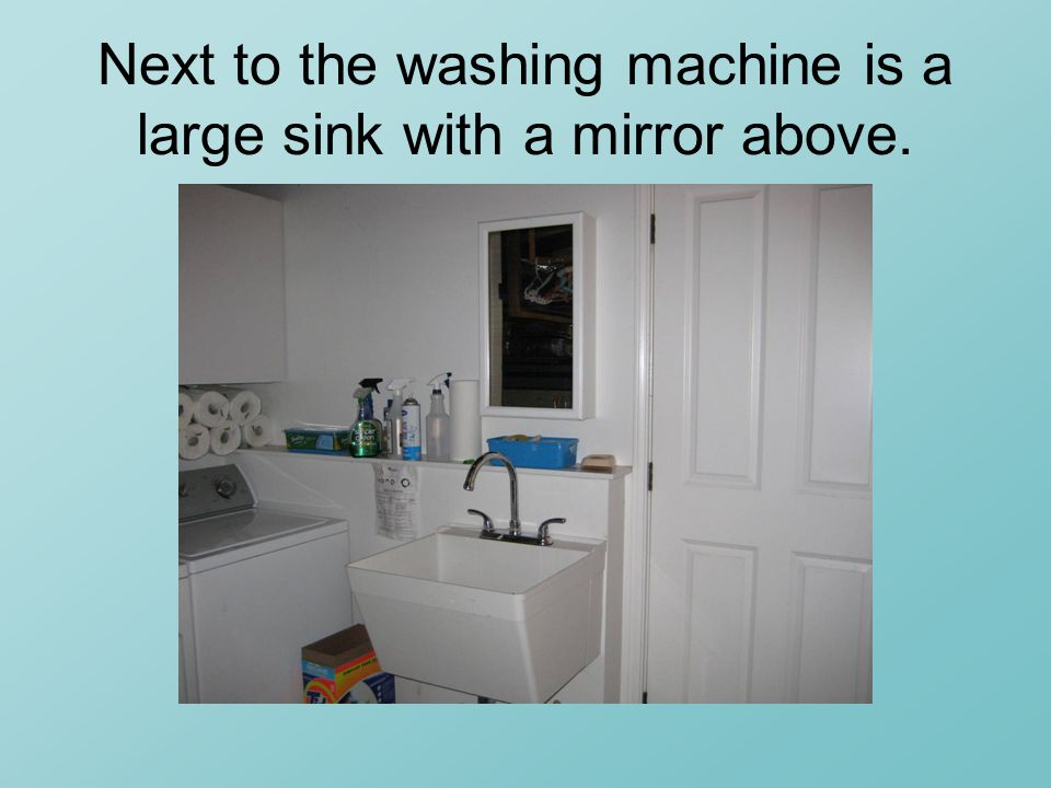 Next to the washing machine is a large sink with a mirror above.