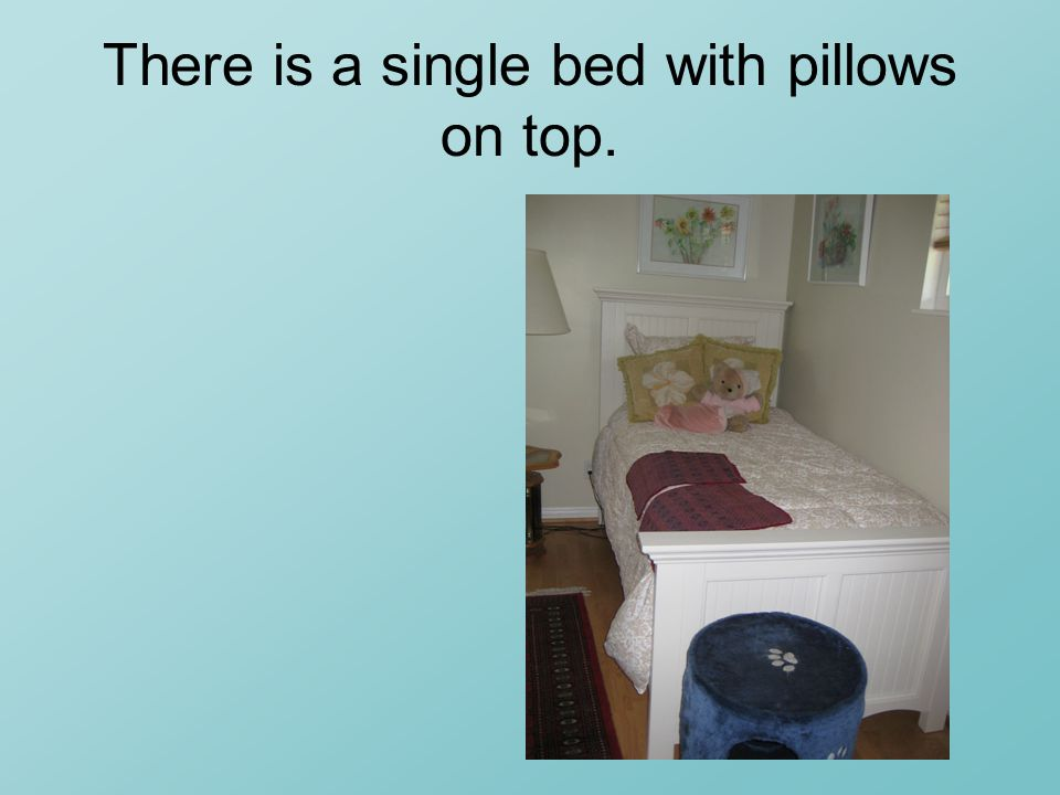 There is a single bed with pillows on top.