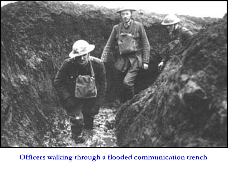 Officers walking through a flooded communication trench