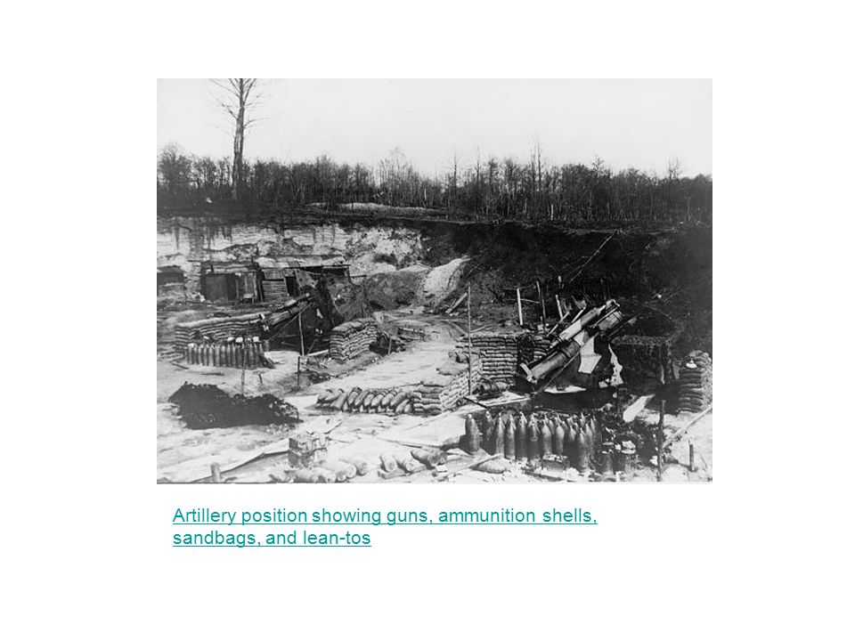 Artillery position showing guns, ammunition shells, sandbags, and lean-tos