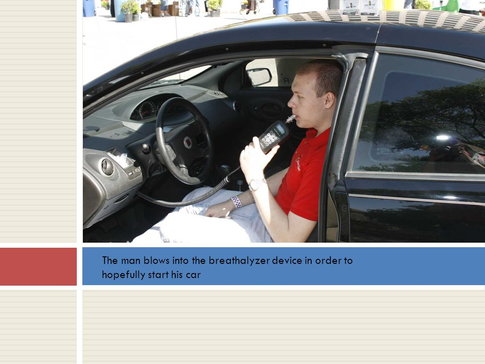 The man blows into the breathalyzer device in order to hopefully start his car