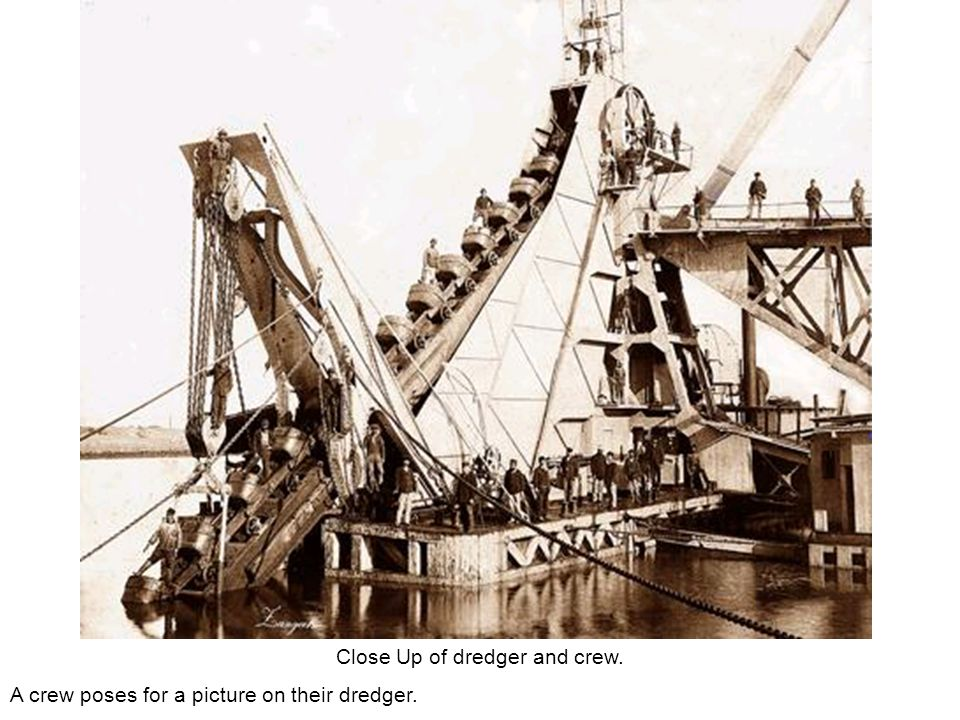 Close Up of dredger and crew. A crew poses for a picture on their dredger.