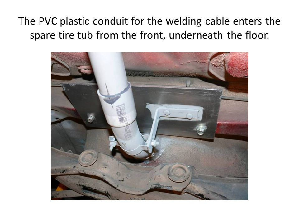 The PVC plastic conduit for the welding cable enters the spare tire tub from the front, underneath the floor.