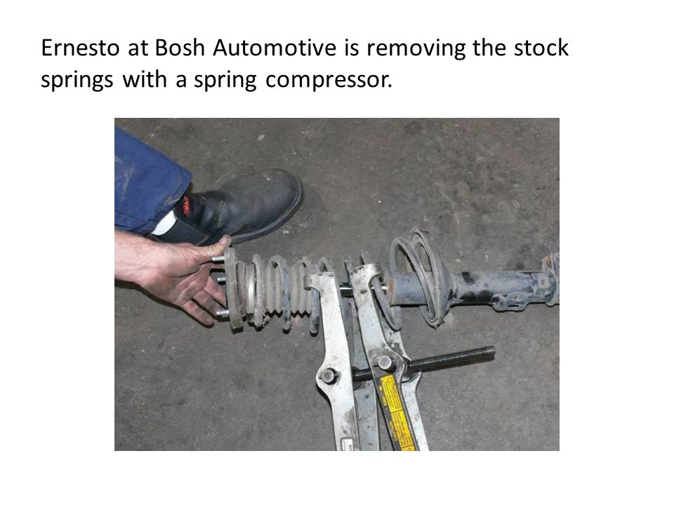 Ernesto at Bosh Automotive is removing the stock springs with a spring compressor.