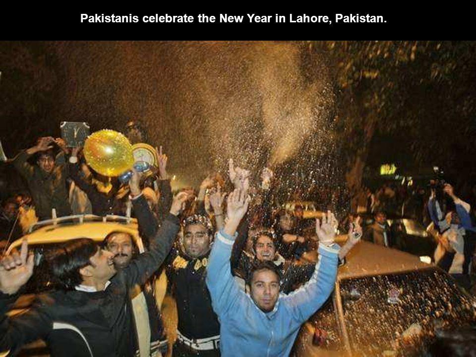 Pakistanis watch the New Year fireworks in Karachi, Pakistan.