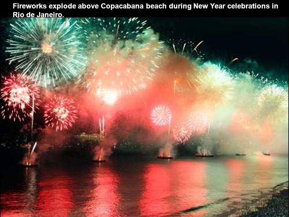 People watch fireworks exploding over Copacabana beach in Rio de Janeiro, Brazil.