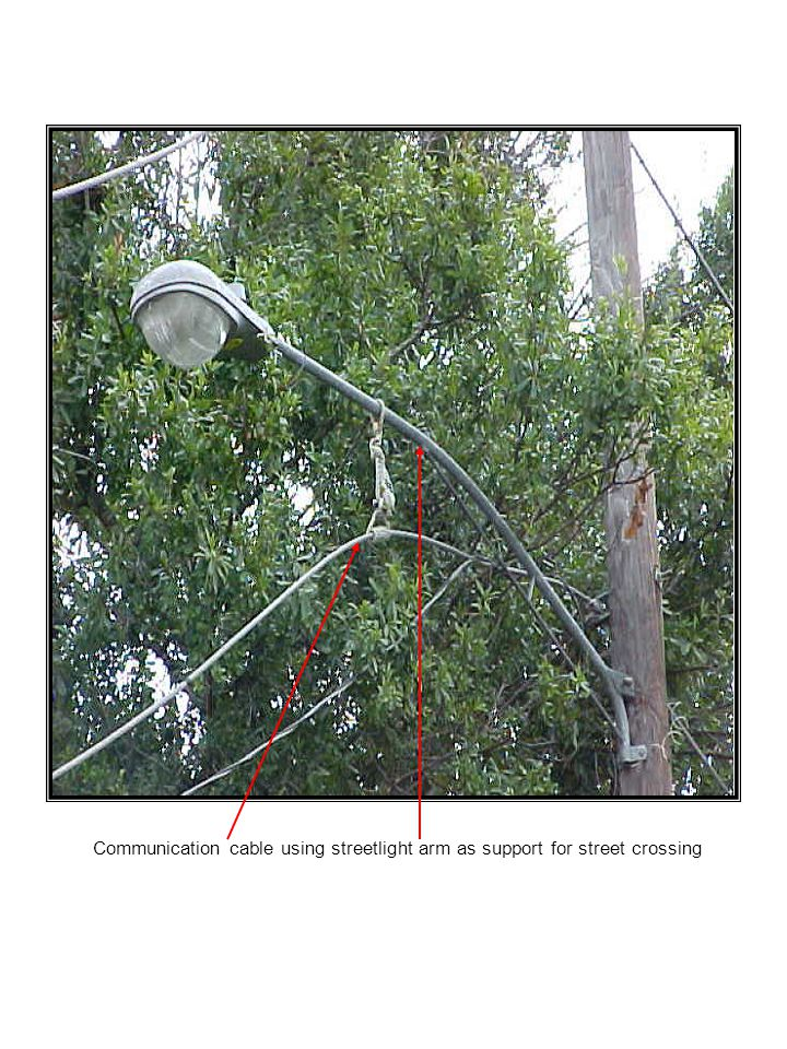 Communication cable using streetlight arm as support for street crossing