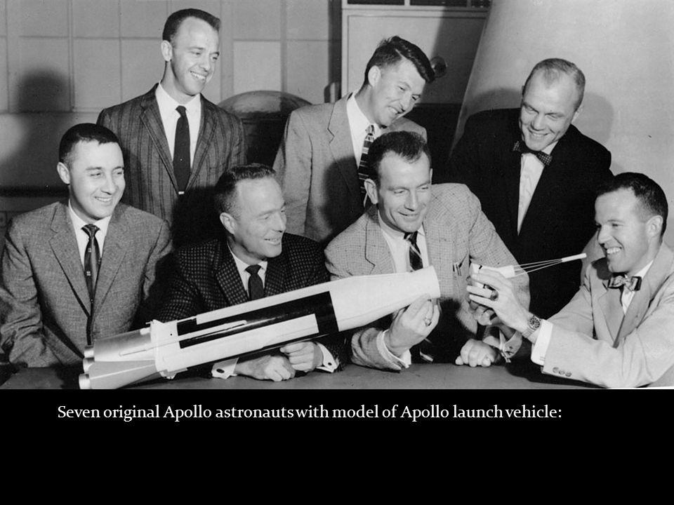 Seven original Apollo astronauts with model of Apollo launch vehicle: