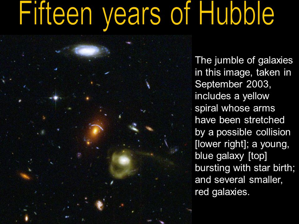 The jumble of galaxies in this image, taken in September 2003, includes a yellow spiral whose arms have been stretched by a possible collision [lower right]; a young, blue galaxy [top] bursting with star birth; and several smaller, red galaxies.
