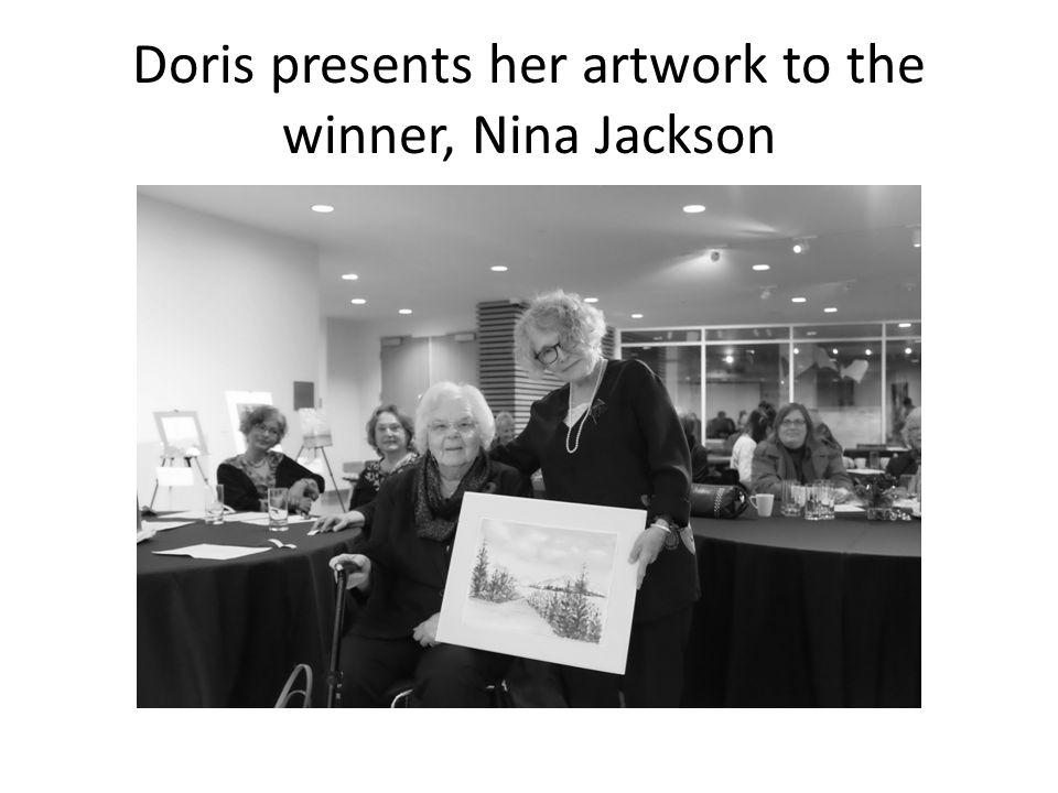 Doris presents her artwork to the winner, Nina Jackson