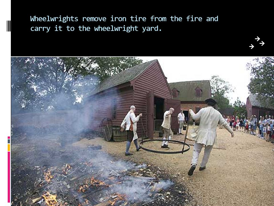 Wheelwrights remove iron tire from the fire and carry it to the wheelwright yard.