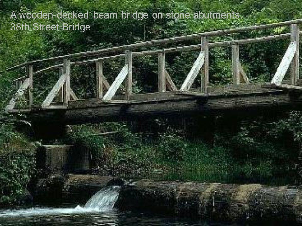 A wooden-decked beam bridge on stone abutments. 38th Street Bridge