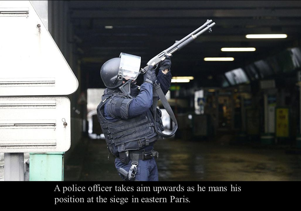 A police officer takes aim upwards as he mans his position at the siege in eastern Paris.