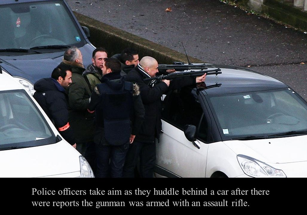 Police officers take aim as they huddle behind a car after there were reports the gunman was armed with an assault rifle.