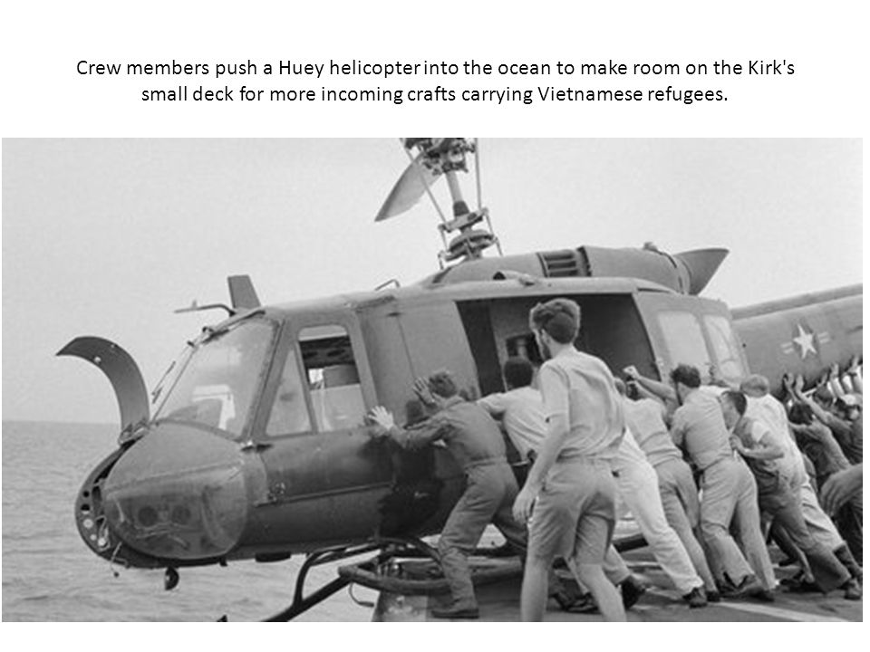 Crew members push a Huey helicopter into the ocean to make room on the Kirk's small deck for more incoming crafts carrying Vietnamese refugees.