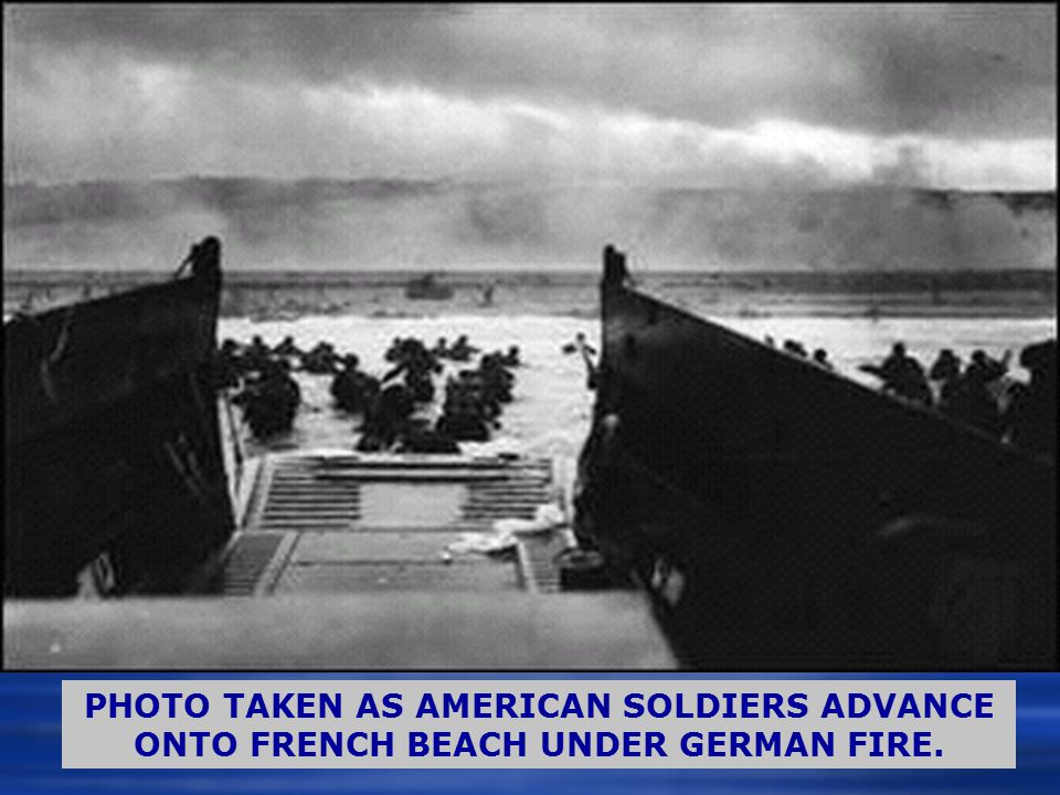 PHOTO TAKEN AS AMERICAN SOLDIERS ADVANCE ONTO FRENCH BEACH UNDER GERMAN FIRE.