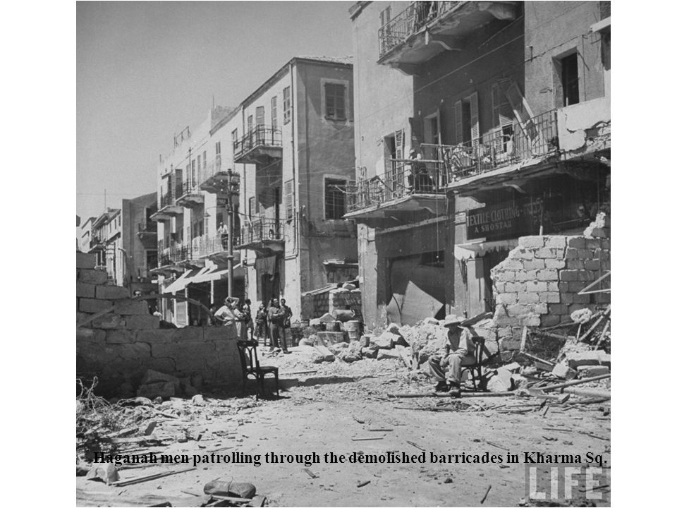 Haganah men patrolling through the demolished barricades in Kharma Sq.