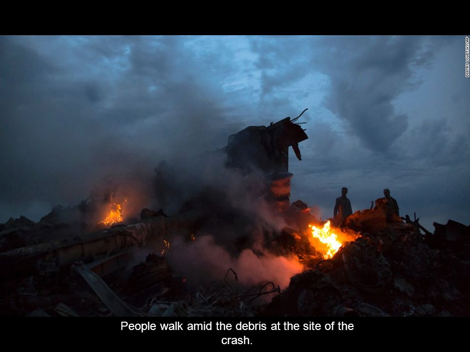 « Previo us Next » People inspect a piece of wreckage believed to be from Malaysia Airlines Flight 17 in Ukraine.