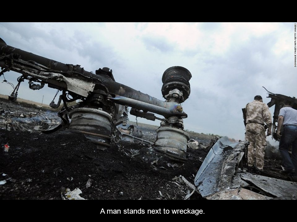 A man stands next to wreckage.