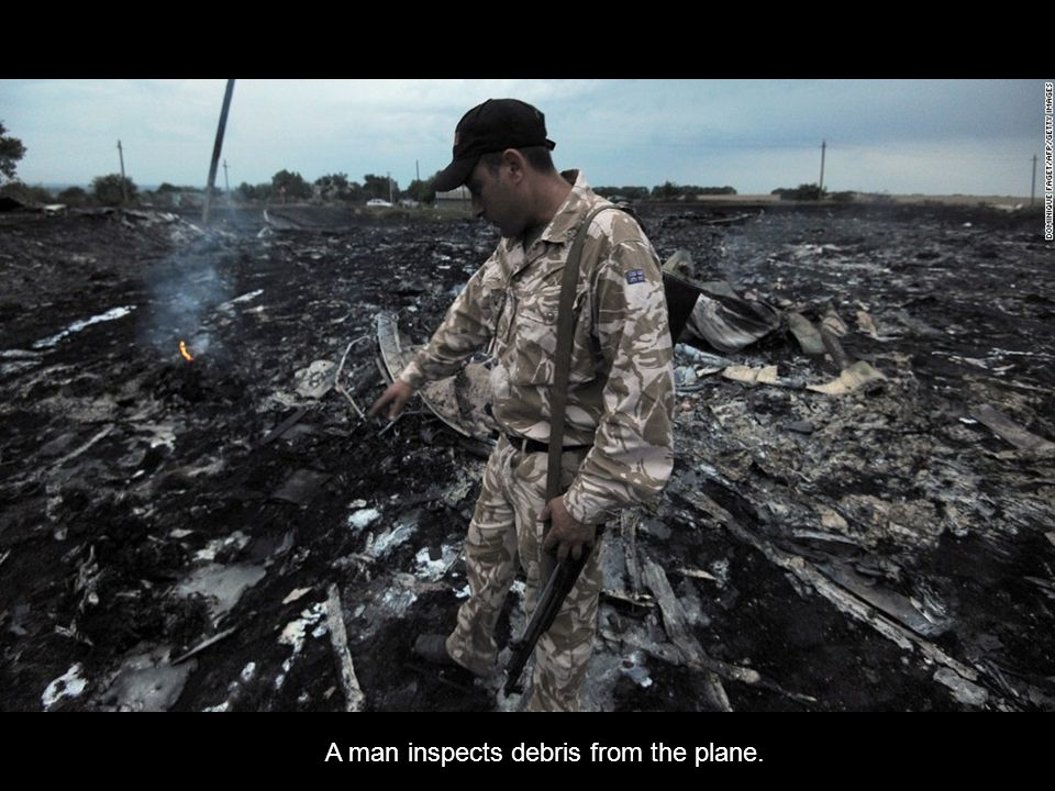 « Previo us Next » A man inspects debris from the plane.