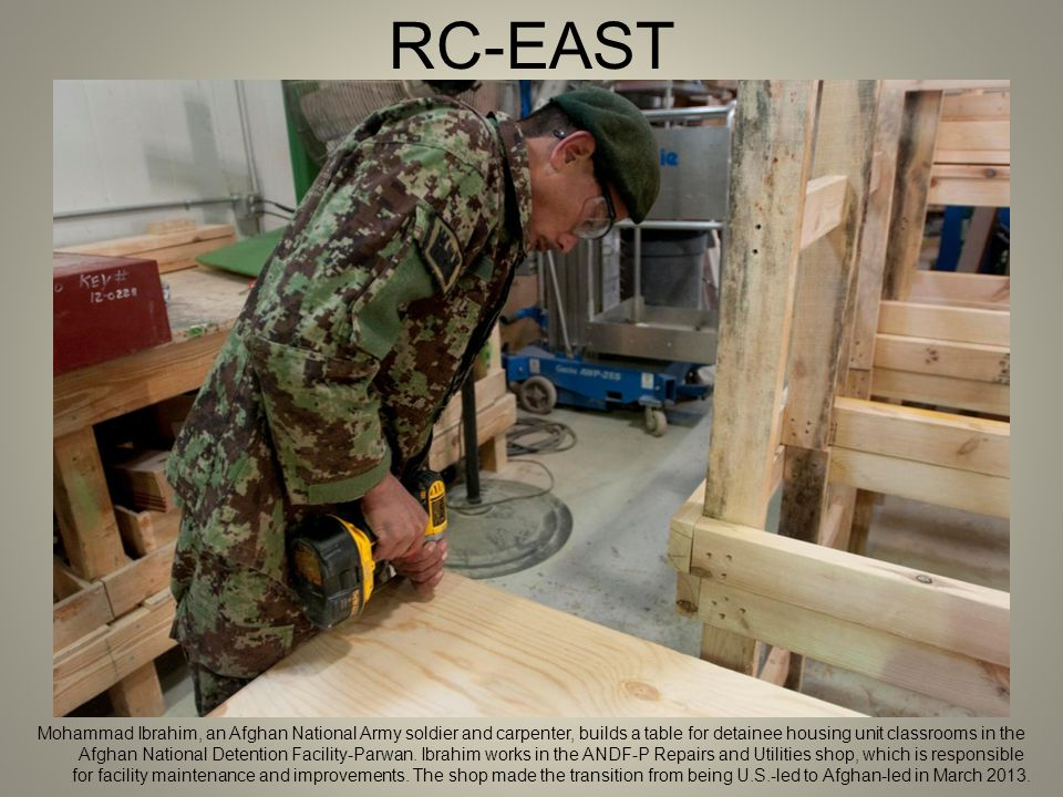 RC-EAST Mohammad Ibrahim, an Afghan National Army soldier and carpenter, builds a table for detainee housing unit classrooms in the Afghan National Detention Facility-Parwan.