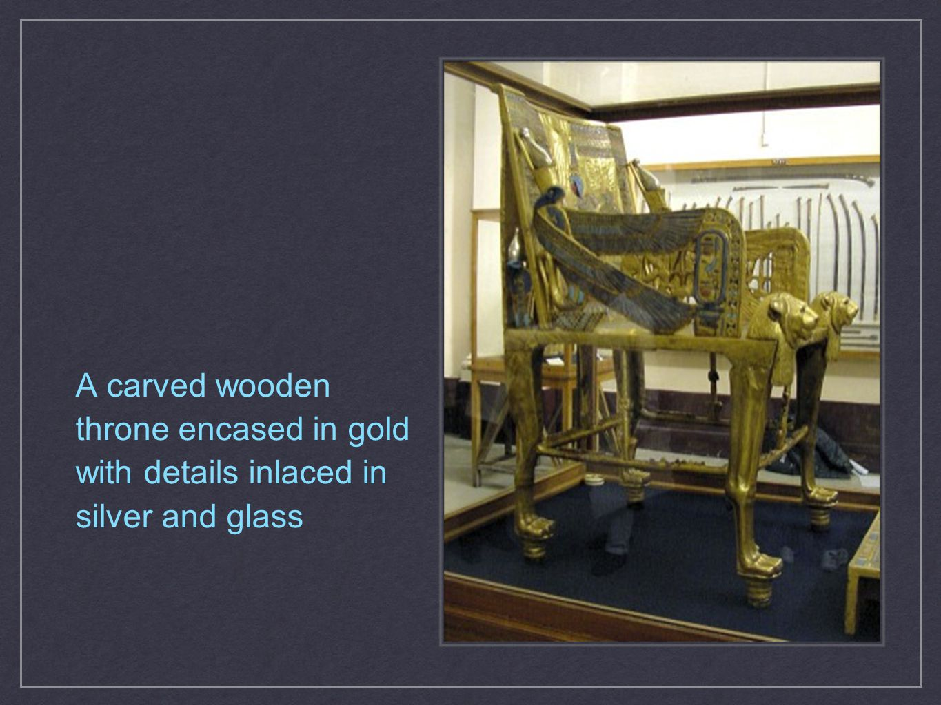 A carved wooden throne encased in gold with details inlaced in silver and glass