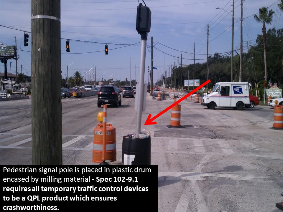 Pedestrian signal pole is placed in plastic drum encased by milling material - Spec 102-9.1 requires all temporary traffic control devices to be a QPL