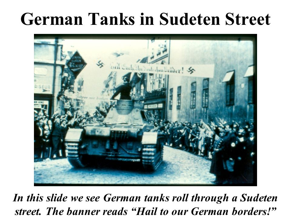 """German Tanks in Sudeten Street In this slide we see German tanks roll through a Sudeten street. The banner reads """"Hail to our German borders!"""""""