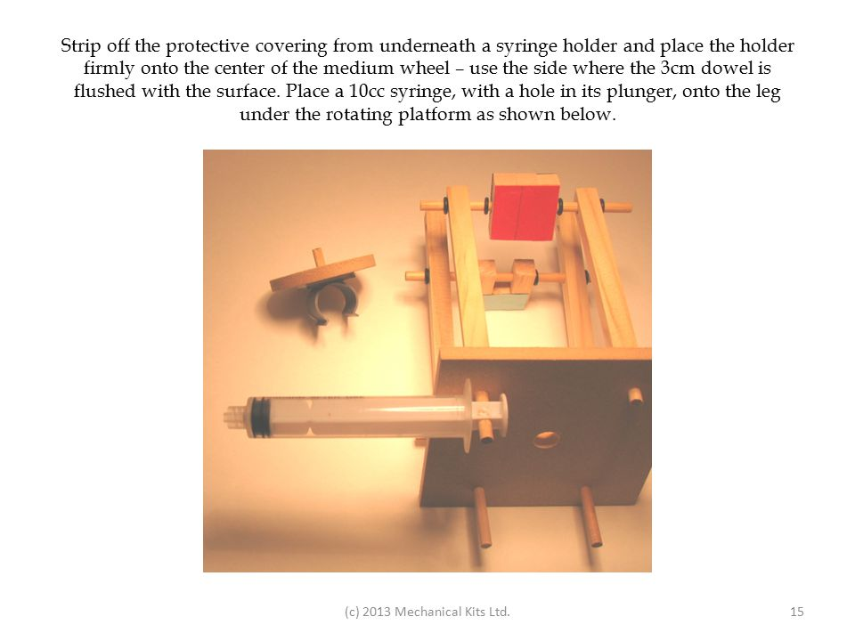 Strip off the protective covering from underneath a syringe holder and place the holder firmly onto the center of the medium wheel – use the side where the 3cm dowel is flushed with the surface.