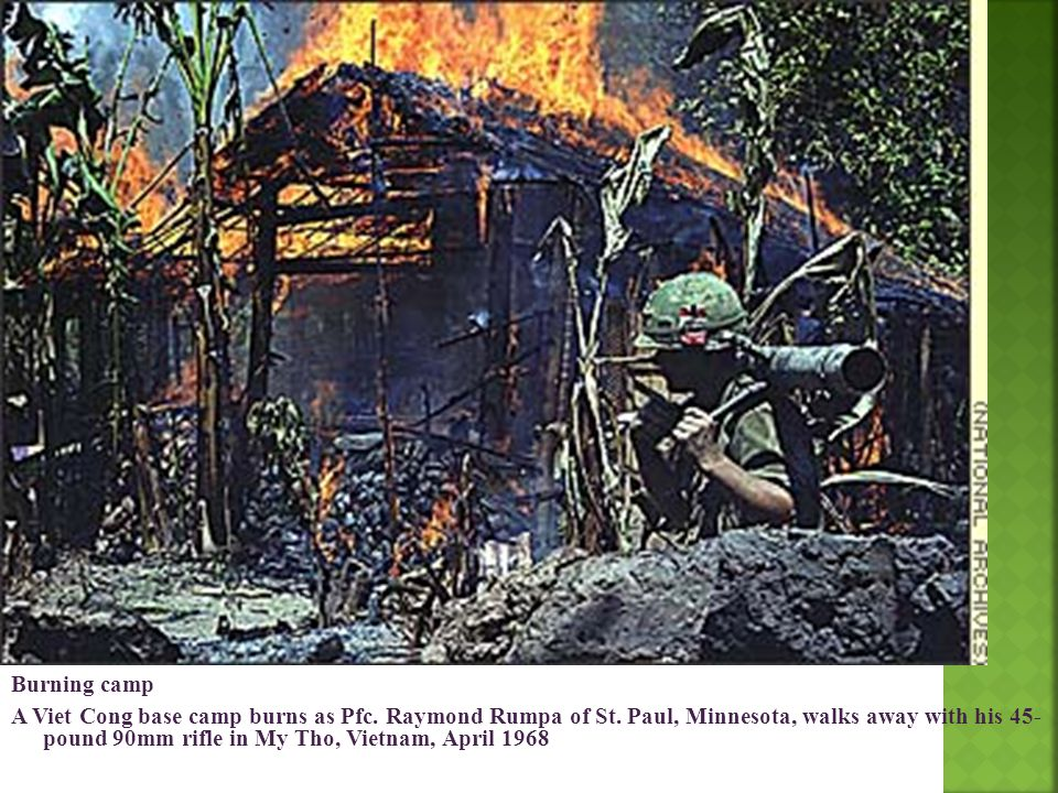 Burning camp A Viet Cong base camp burns as Pfc. Raymond Rumpa of St. Paul, Minnesota, walks away with his 45- pound 90mm rifle in My Tho, Vietnam, Ap