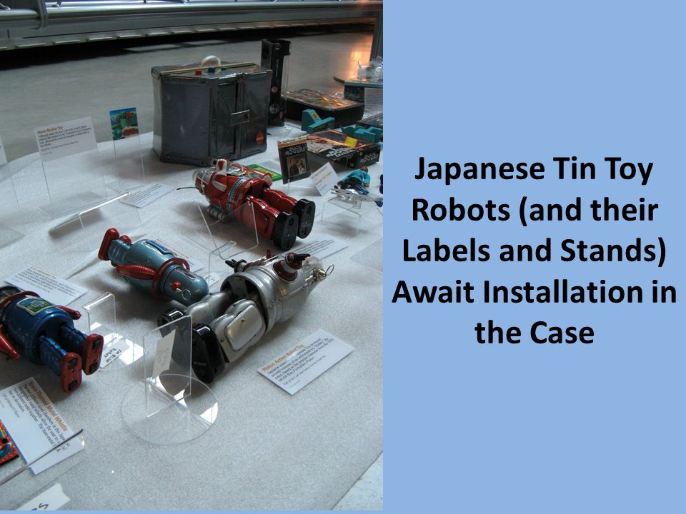 Japanese Tin Toy Robots (and their Labels and Stands) Await Installation in the Case