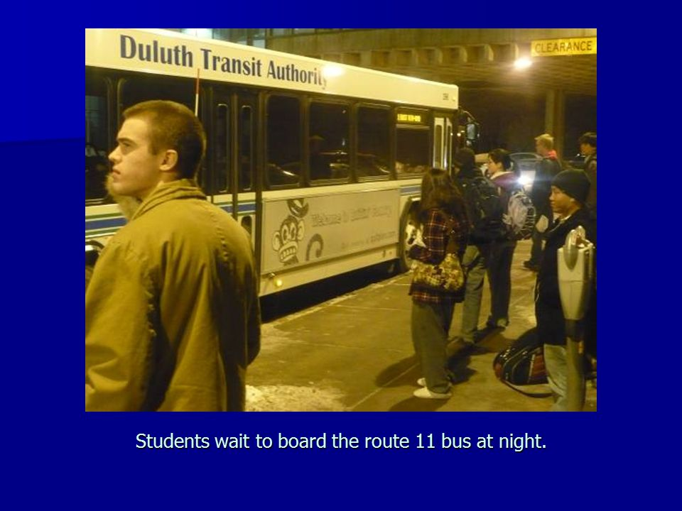 Students wait to board the route 11 bus at night.